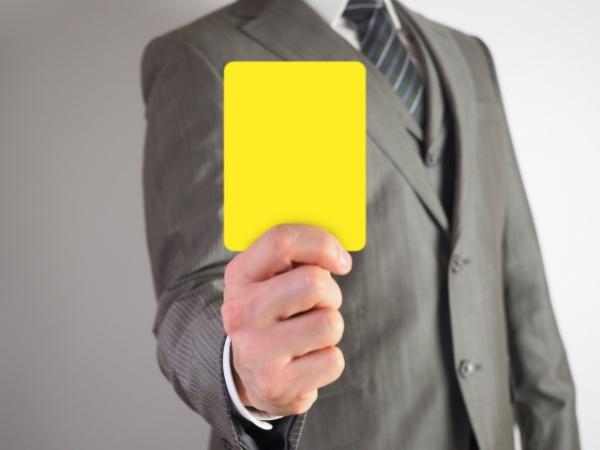 イエローカードを持ち出すビジネスマン